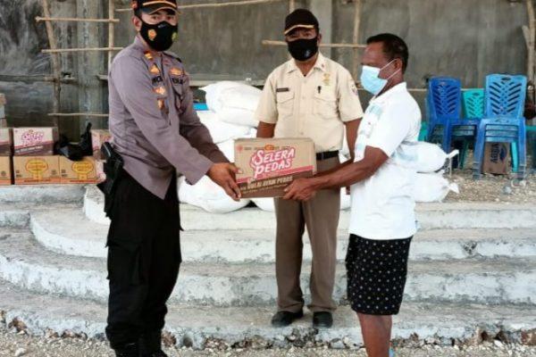 Kapolsek Kupang Timur saat meyerahkan bantuan kepada perwakilan masyarakat (ist)