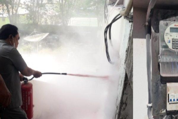 Seorang anggota dewan saat menyemprot meteran yang meledak menggunakan apar serta meteran listrik yang baru setelah diganti PLN (yandry/kupangterkini.com)